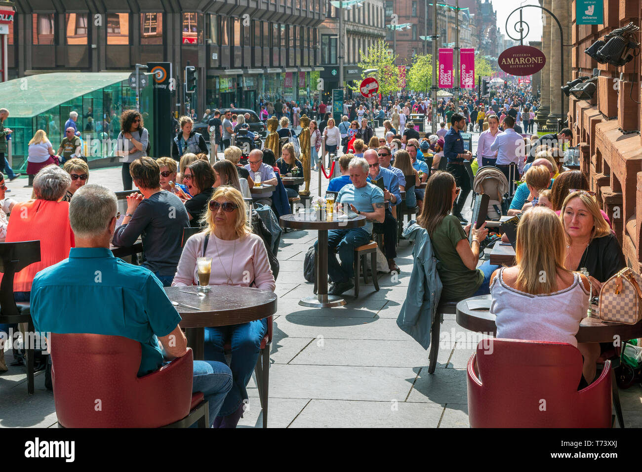 People sitting at outdoor tables at a restaurant in Buchanan Street, Glasgow, Scotland, UK - Stock Image