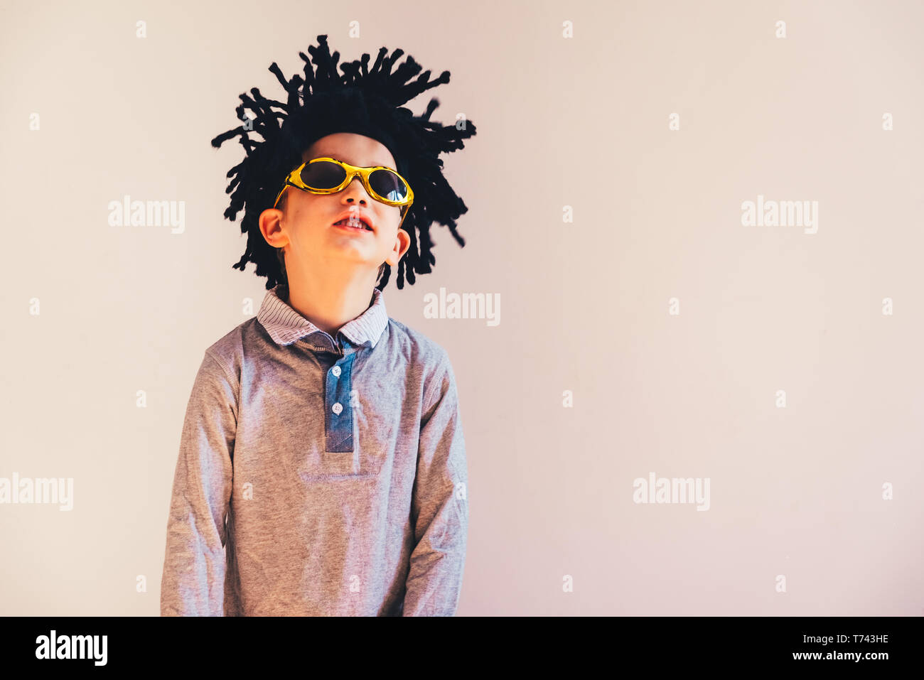 Child with rastafari wig dancing cheerful, isolated copy space white background. - Stock Image