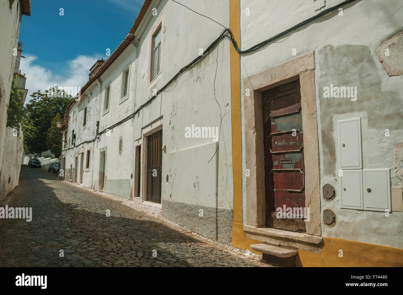 Old Houses With Doors On Alley With Cobblestone Pavement In Sunny