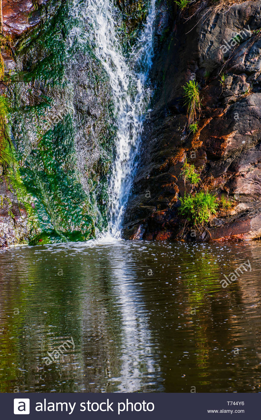 A beautiful waterfall in the nature. Water splashing down into a lake, reflections of the cascade on the surface. - Stock Image