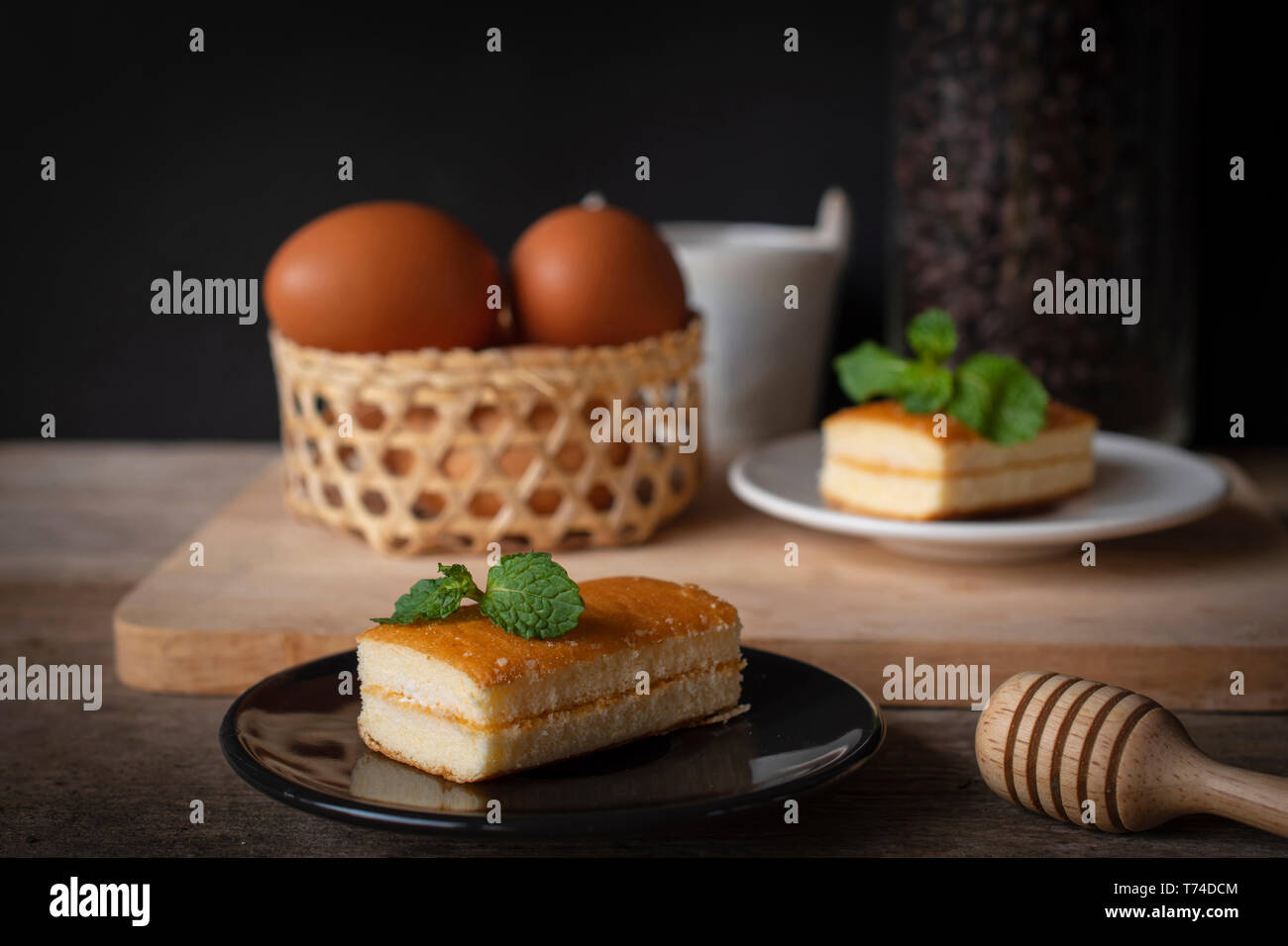 layer vanilla flavoured cake place on black plate on the wooden table there are white plate and coffee bean in glass bottles and bucket of water ceram Stock Photo