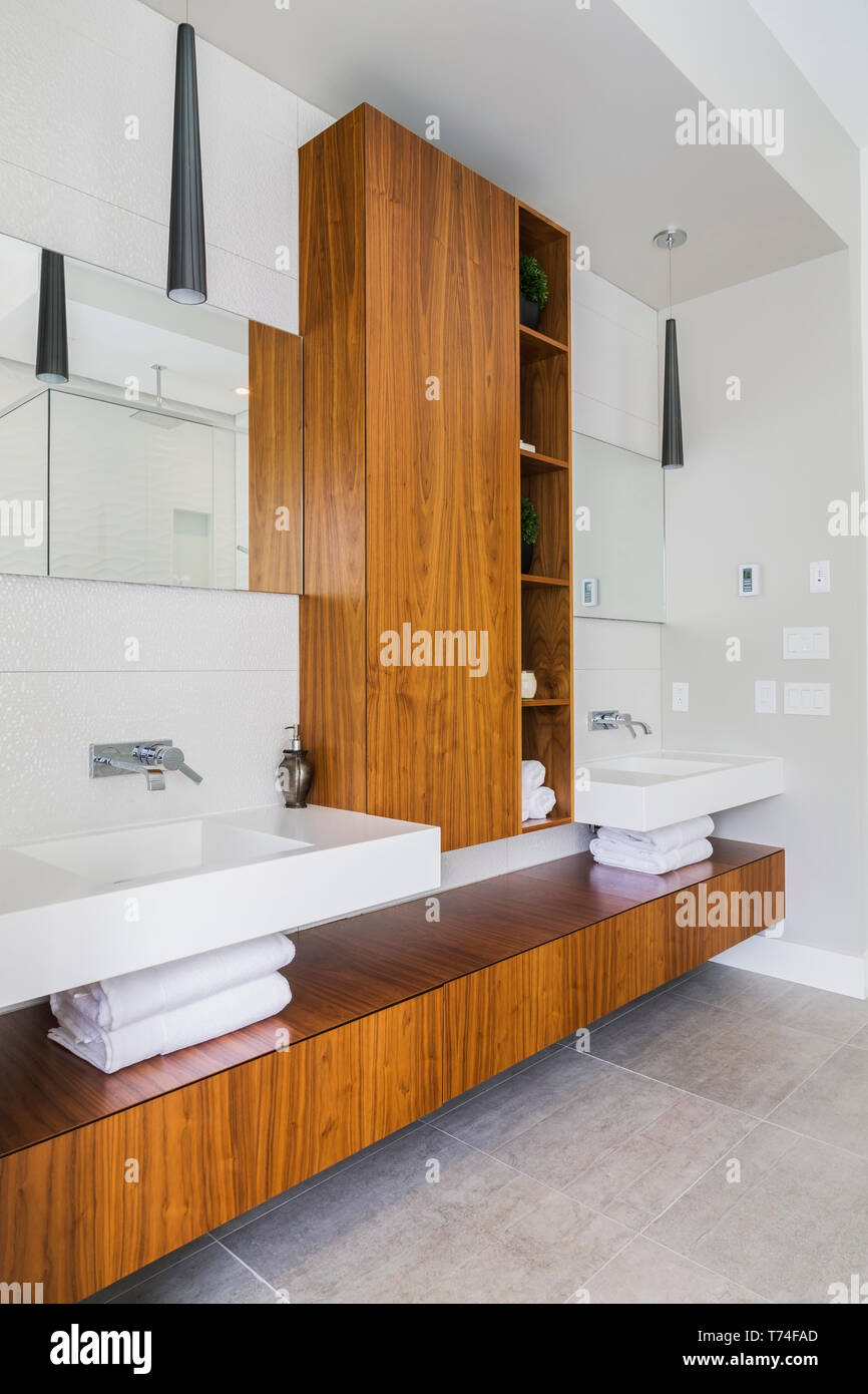 Walnut Wood Vanity And White Corian Sinks In Grey Ceramic Tile Floor En Suite Inside A Luxurious Contemporary Bungalow Style Home Quebec Canada Stock Photo Alamy
