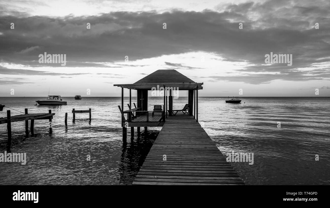 Black and white image of a dock with seating and boats mooring on the tranquil water at sunset; Roatan, Bay Islands Department, Honduras Stock Photo