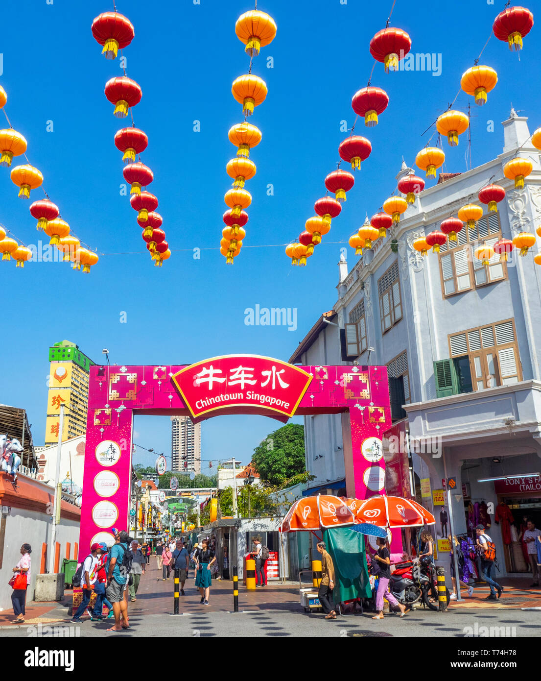 Chinese red lanterns for Chinese New Year celebrations  and tourists at gateway arch entrance to Pagoda Street Chinatown Singapore. Stock Photo