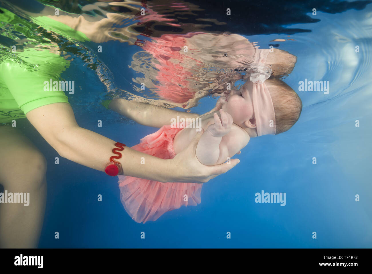 Odessa, Ukraine, Eastern Europe. 23rd Apr, 2019. Little baby girl learning to swim underwater in a swimming pool, mother holding the child. Healthy family lifestyle and children water sports activity. Child development, disease prevention Credit: Andrey Nekrasov/ZUMA Wire/Alamy Live News - Stock Image
