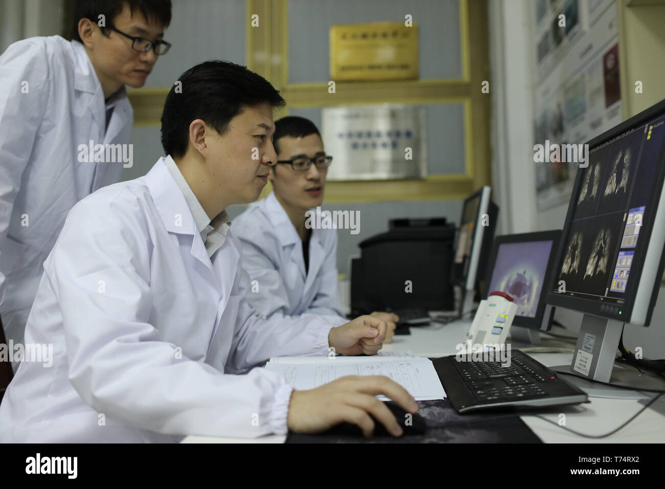 (190504) -- WUHAN, May 4, 2019 (Xinhua) -- Zhou Xin (C) discusses with his colleagues about the quality of human lung magnetic resonance images at Wuhan Institute of Physics and Mathematics of Chinese Academy of Sciences in Wuhan, capital of central China's Hubei Province, April 18, 2019. Professor Zhou Xin is the deputy director of Wuhan Institute of Physics and Mathematics of Chinese Academy of Sciences, State Key Laboratory of Magnetic Resonance and Atomic and Molecular Physics, and National Center for Magnetic Resonance in Wuhan. He is interested in ultrasensitive magnetic resonance imagin - Stock Image