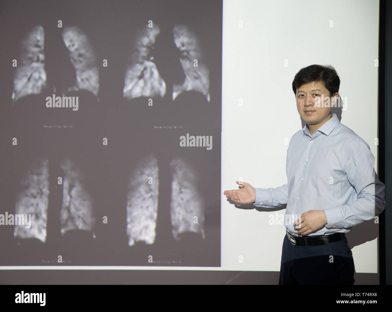 (190504) -- WUHAN, May 4, 2019 (Xinhua) -- Zhou Xin poses for a photo with human lung magnetic resonance images at Wuhan Institute of Physics and Mathematics of Chinese Academy of Sciences in Wuhan, capital of central China's Hubei Province, April 19, 2019. Professor Zhou Xin is the deputy director of Wuhan Institute of Physics and Mathematics of Chinese Academy of Sciences, State Key Laboratory of Magnetic Resonance and Atomic and Molecular Physics, and National Center for Magnetic Resonance in Wuhan. He is interested in ultrasensitive magnetic resonance imaging (MRI) instruments, techniques  - Stock Image