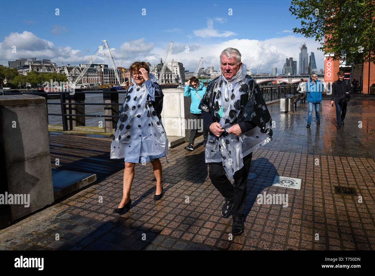 London, UK.  4 May 2019.  UK Weather: Tourists wearing rain ponchos walk on the South Bank after rain clouds brought a shower to central London.  The Bank Holiday weather is forecast to remain cool and potentially, the coldest May Bank Holiday on record.  Credit: Stephen Chung / Alamy Live News - Stock Image