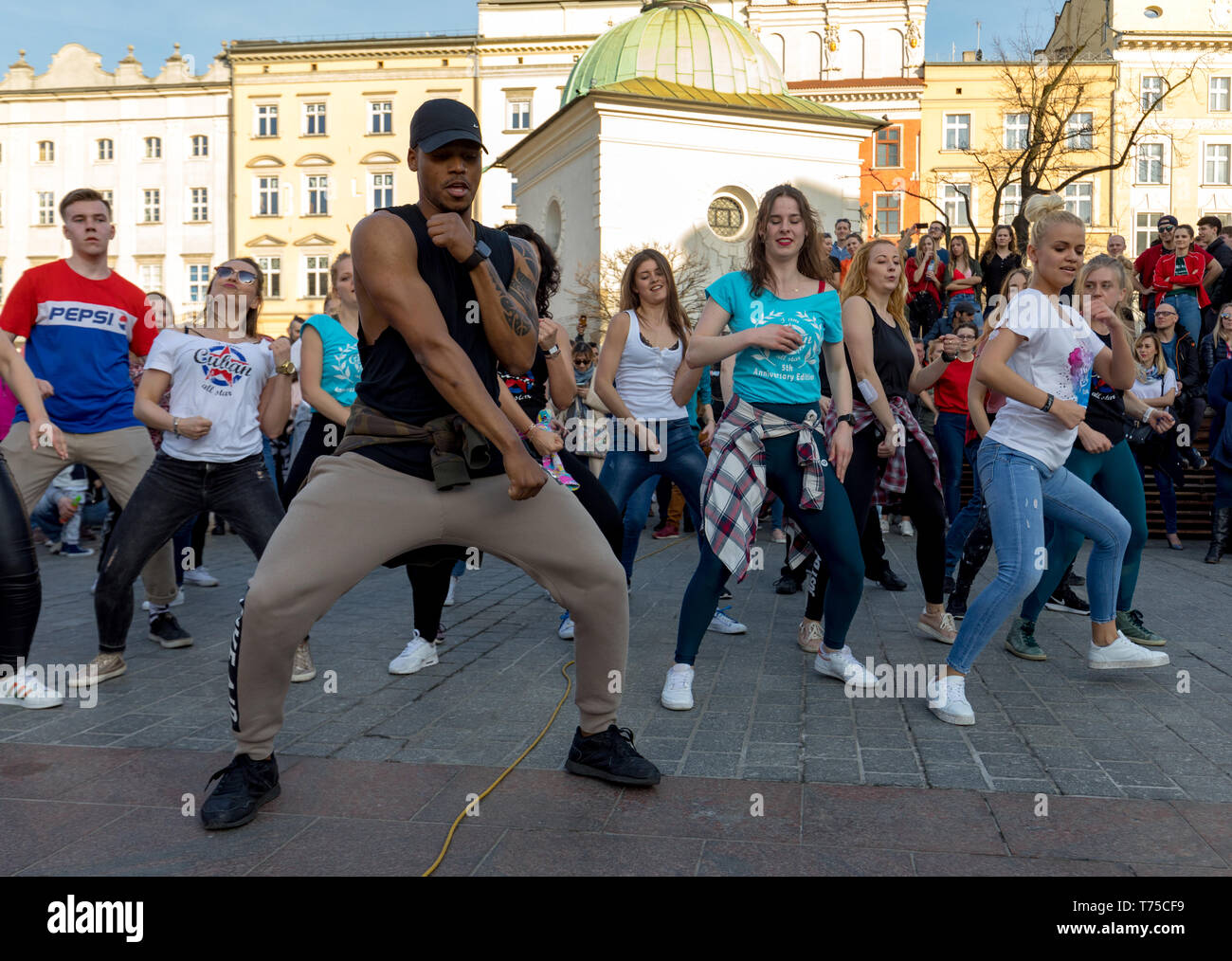 Cracow, Poland - March 30, 2019:  International Flashmob Day of Rueda de Casino. Several hundred persons dance Hispanic rhythms on the Main Square in  - Stock Image