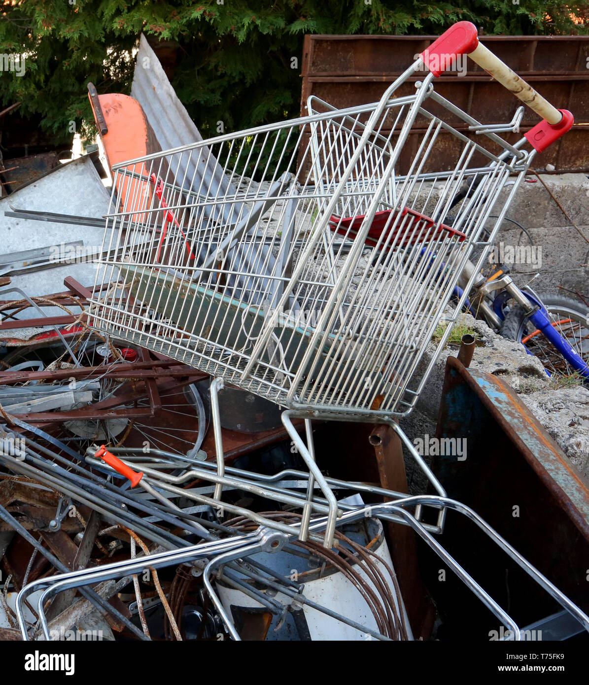 old supermarket shopping cart in the large dump of old and unusable ferrous material - Stock Image