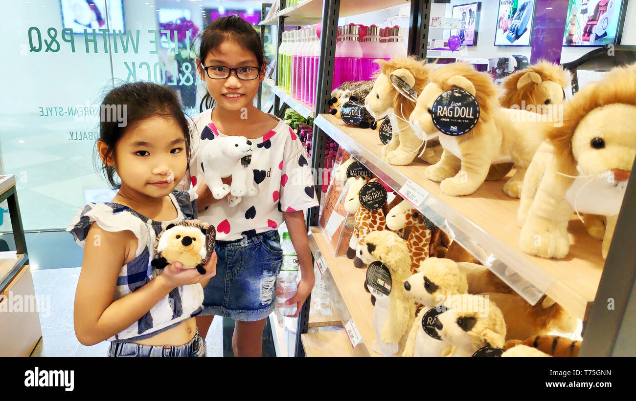 Two cute Vietnamese Asian girls smiling choosing brown lions stuff animals on shelf for birthday gift in Supermarket Stock Photo