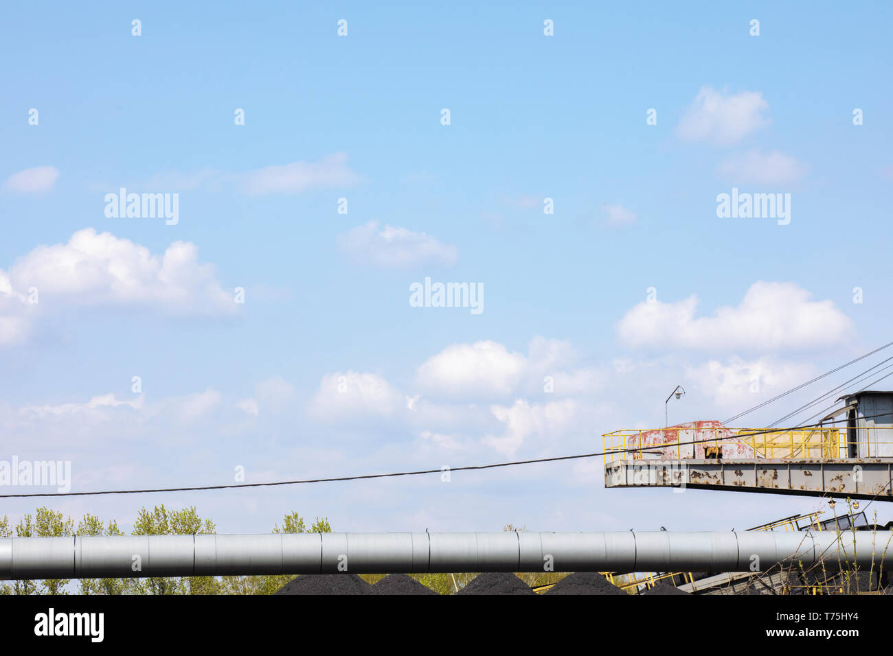 Ramp for loading coal. Old industrial architecture. Long silver pipe. Blue sky. Horizontal composition, copy space.  Kopalnia Wujek. Katowice Poland. Stock Photo
