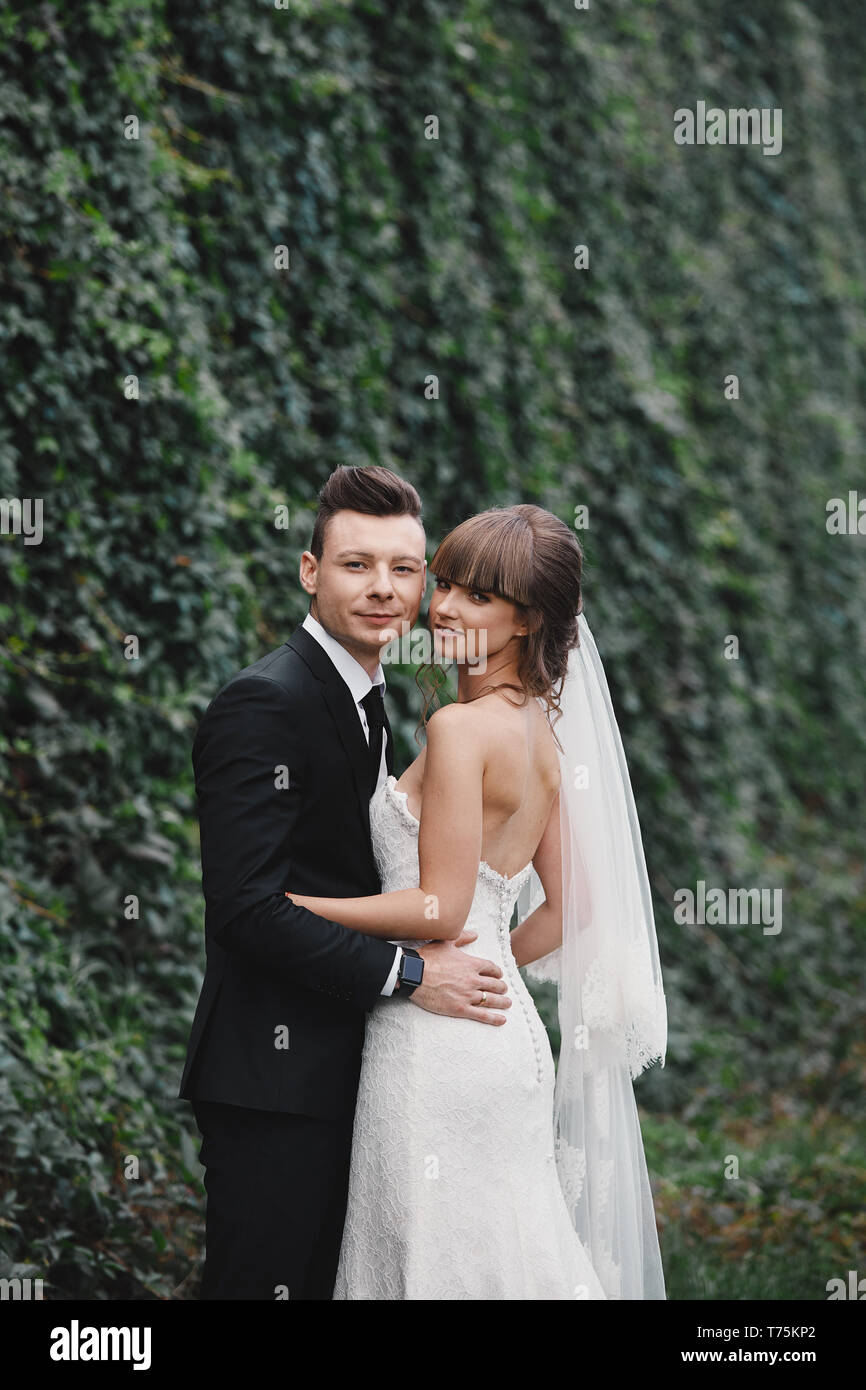 Romantic happy couple newlyweds, bride and groom stands and holding bouquet of pink and purple flowers and greens, greenery with ribbon in the garden. - Stock Image