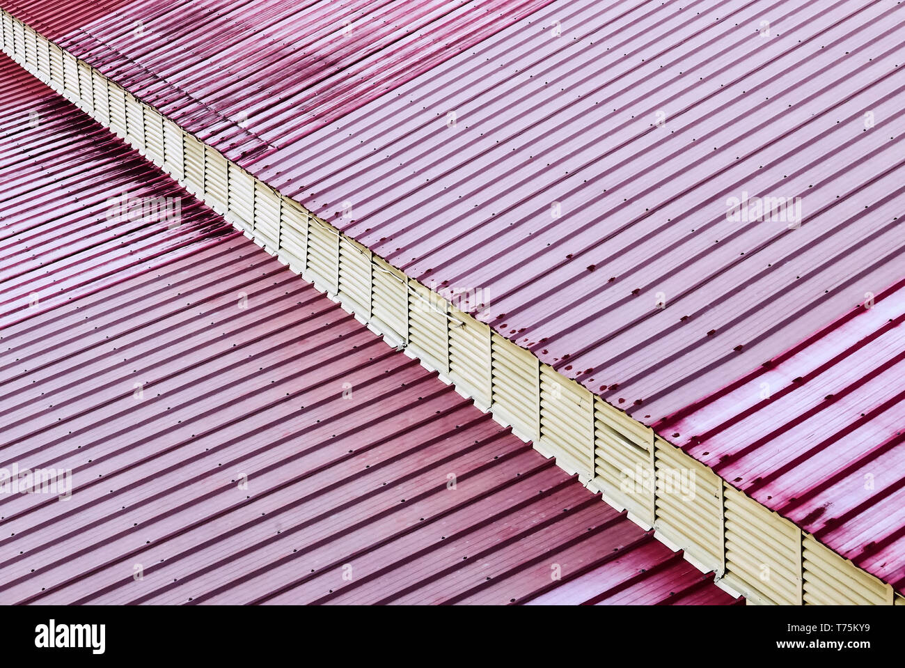 Detail view of a roof made of red colored metal sheets. A diagonal overhang gives a 3-dimensional impression. - Stock Image