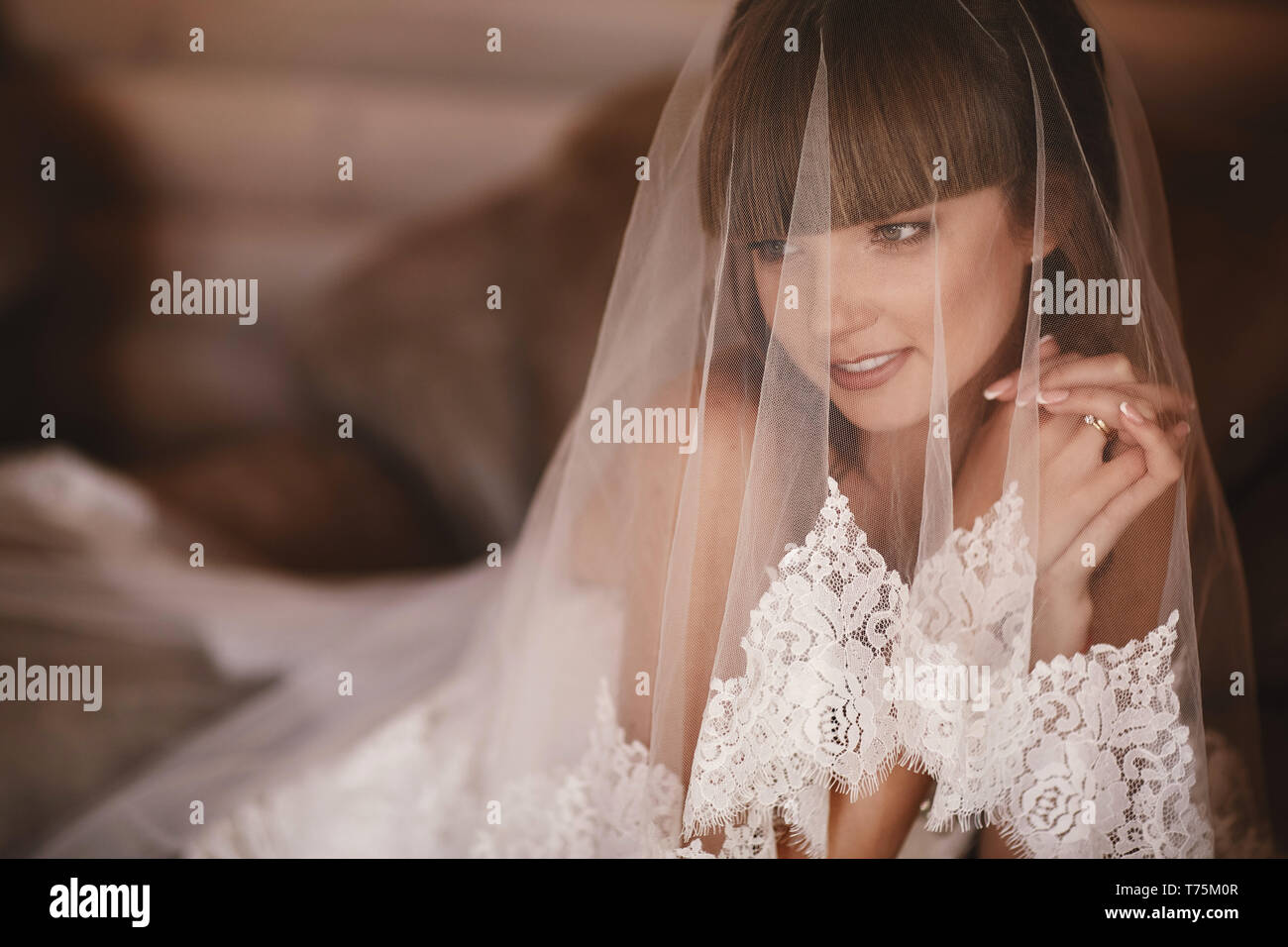 Portrait of charming bride sitting on the bed in a hotel room. the bride is covered with veil. Close up. Wedding morning. Gentle, Tender emotion on th Stock Photo