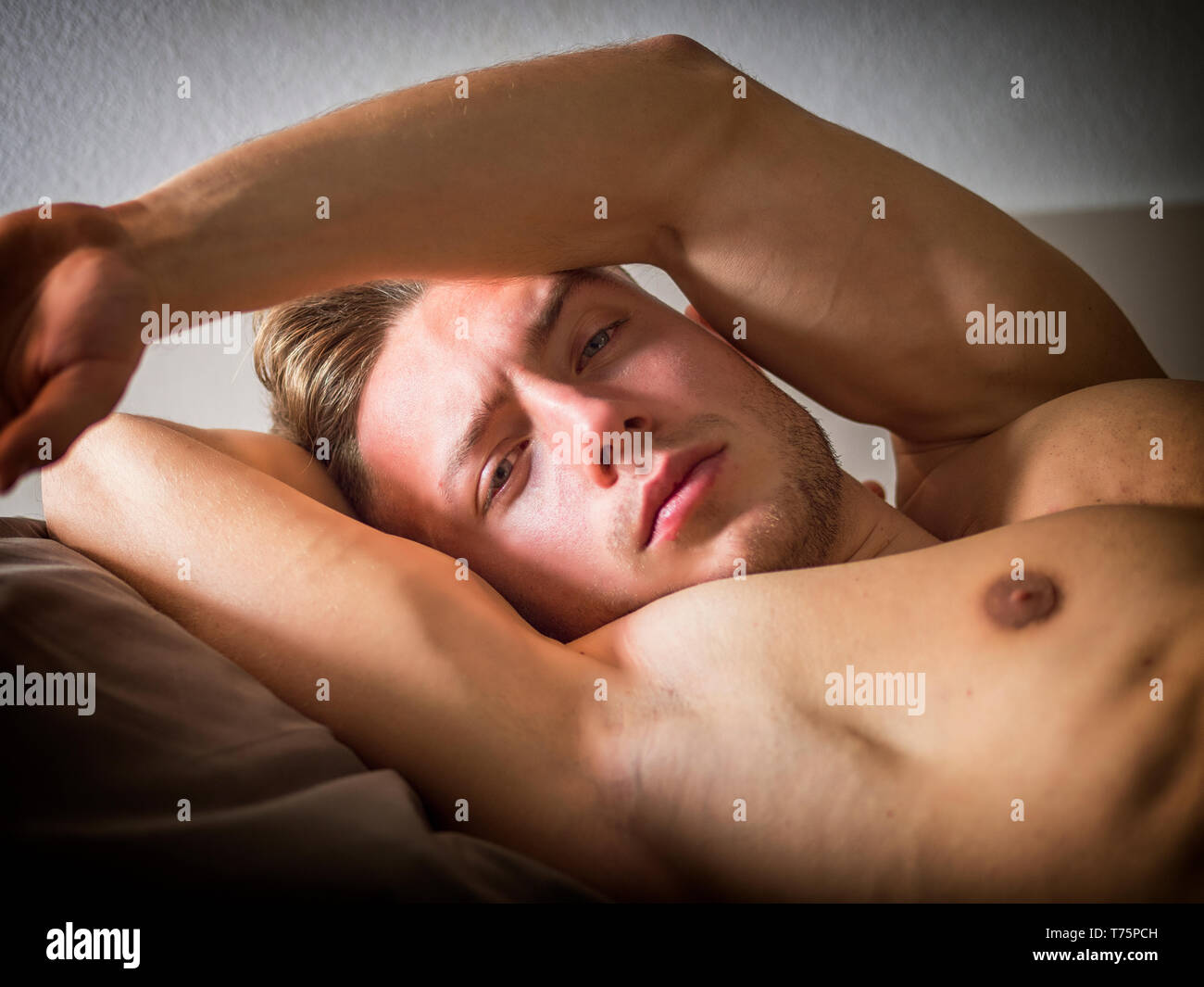 Shirtless sexy male model lying alone on his bed in his bedroom, looking at camera with a seductive attitude Stock Photo