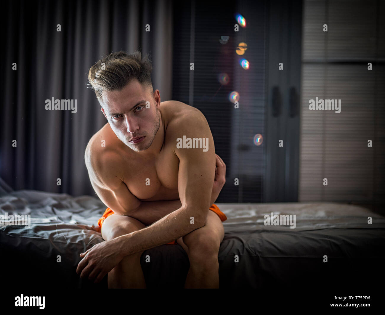 Shirtless naked sexy male model sitting alone on his bed in his bedroom, looking at camera with a seductive attitude Stock Photo