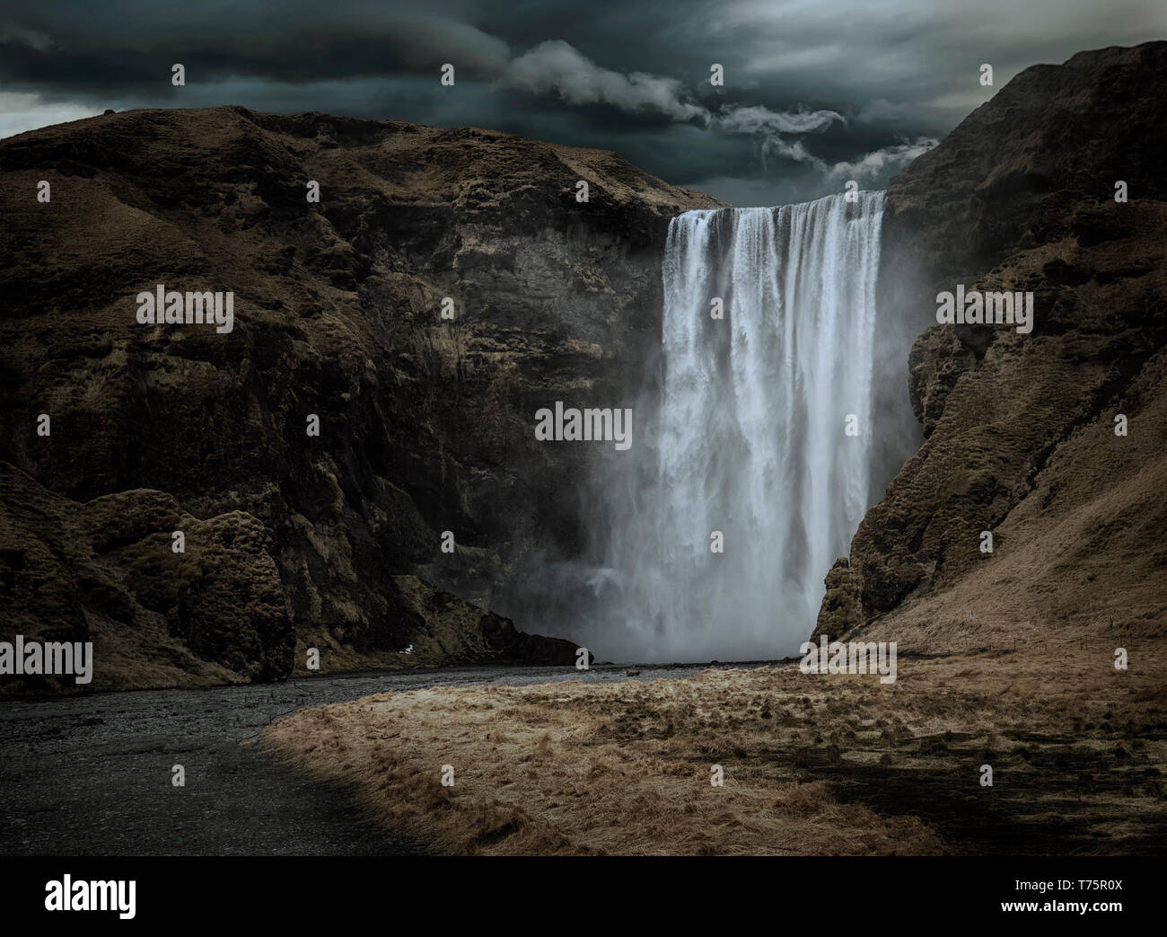 Majestic and dark Skogafoss waterfall in Iceland in a stormy day, moody atmosphere Stock Photo