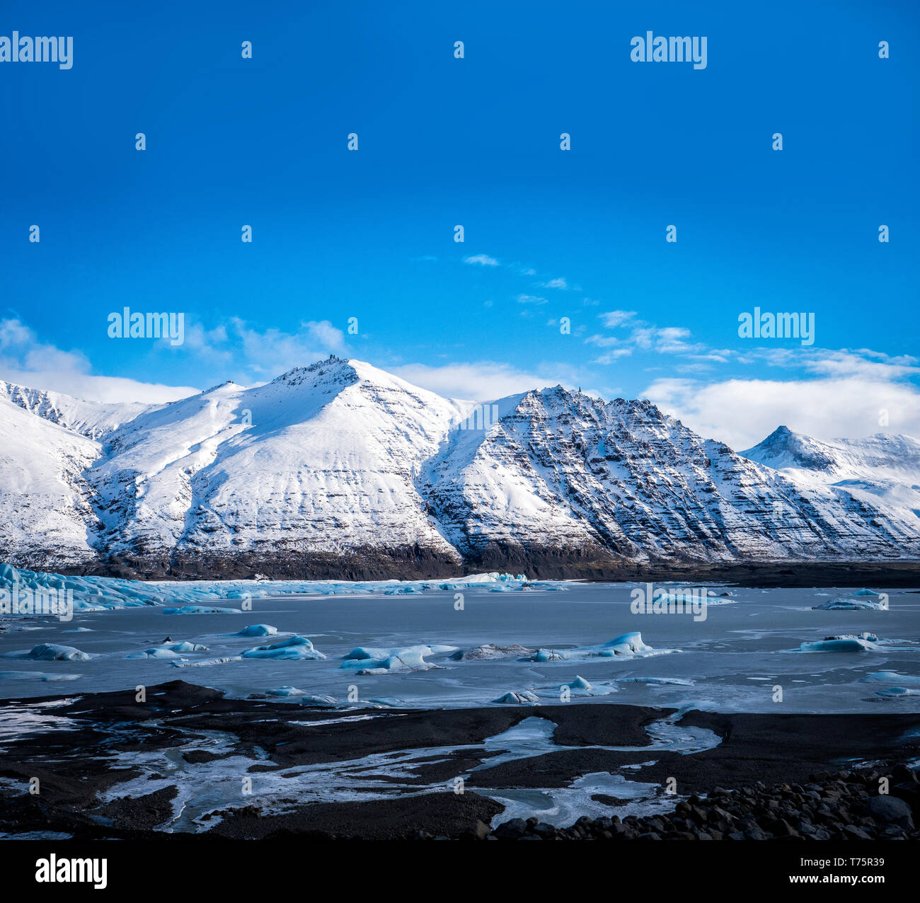 Huge majestic glacier's icy surface by snowy mountain in Iceland Stock Photo