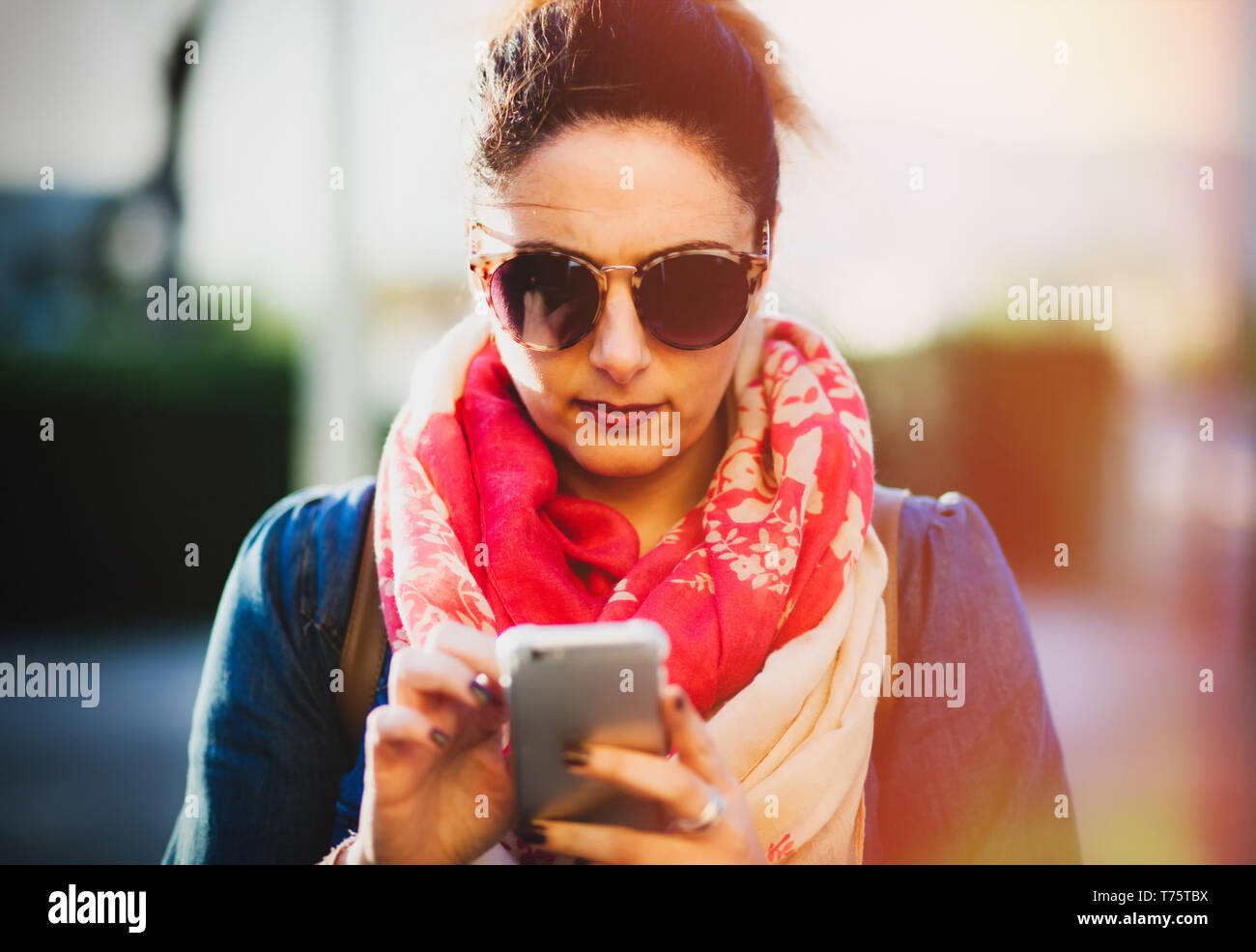Young woman using mobile phone outdoors in spring. - Stock Image
