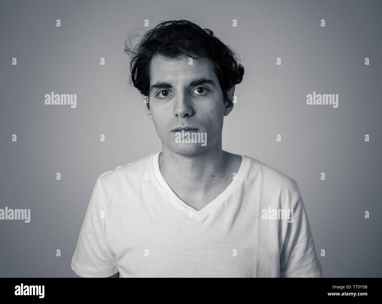Black and white portrait of young caucasian male feeling furious. Looking displeased and annoyed . Studio shot. In people and facial expressions and n - Stock Image