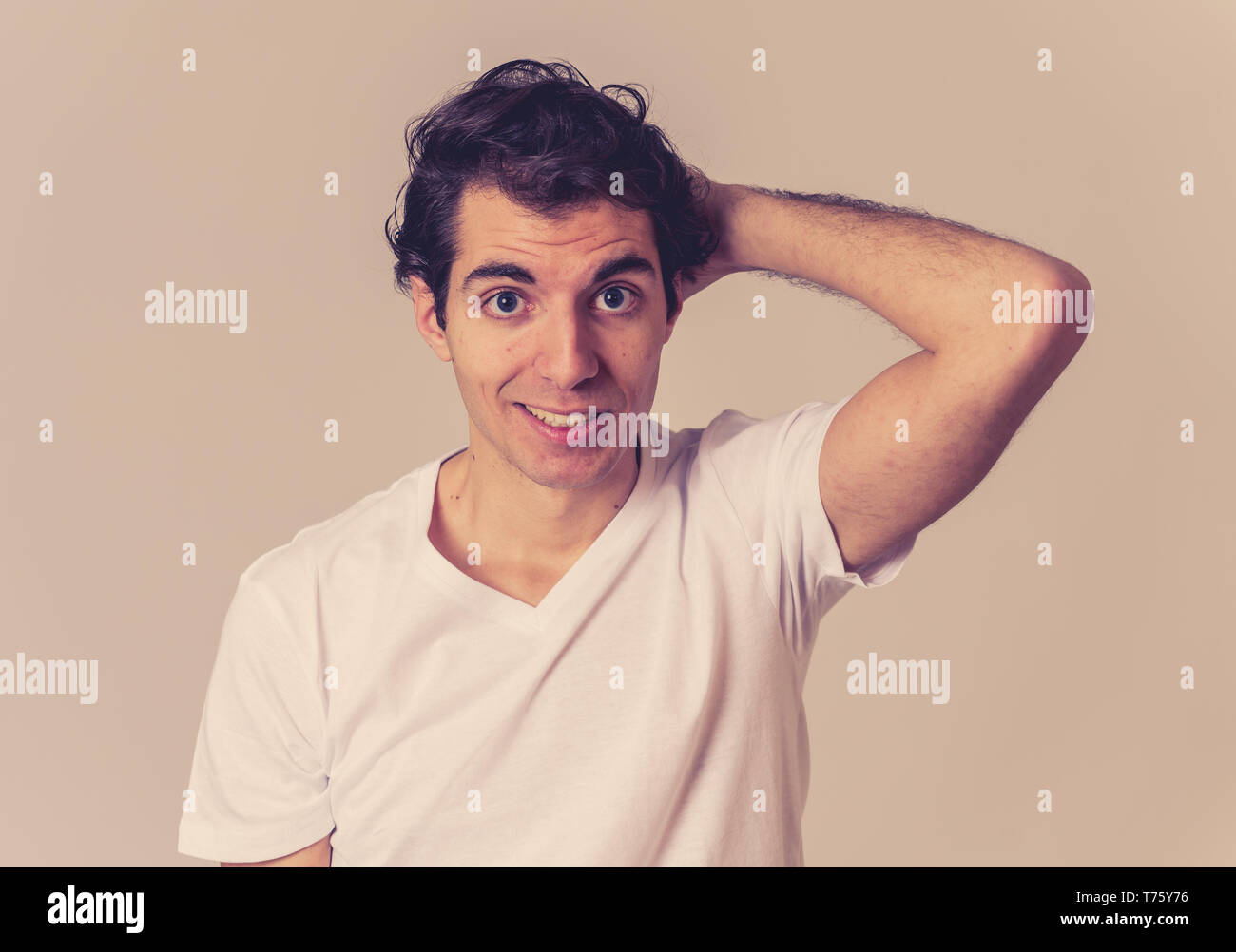 Close up portrait of funny young man looking embarrassed feeling ashamed and shy isolated against neutral background in People, human emotions and exp - Stock Image