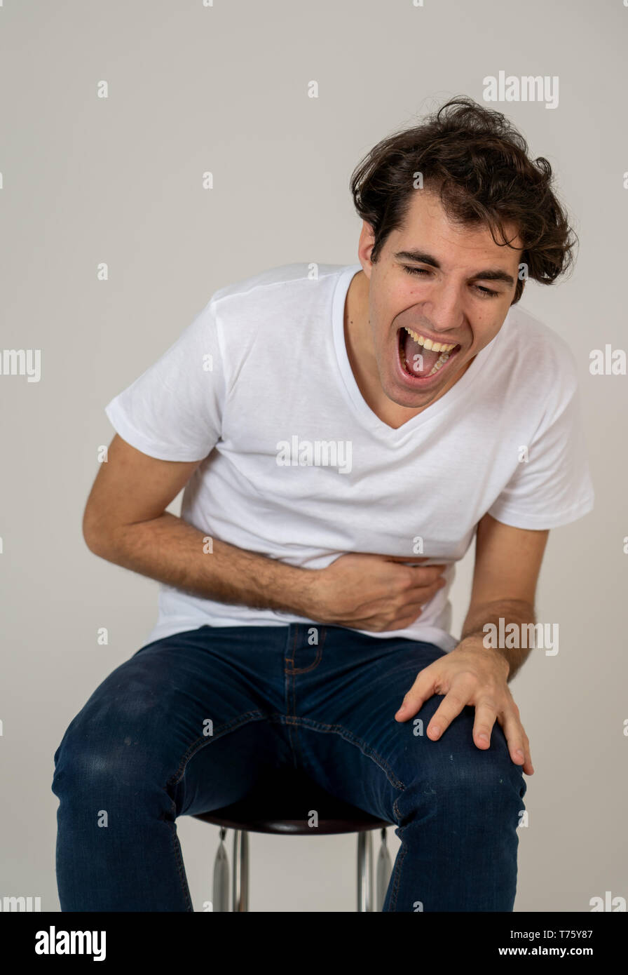Portrait of young millennial funny male having fun bursting into laughing loudly after hearing humor anecdotes and jokes. Isolated against neutral bac - Stock Image