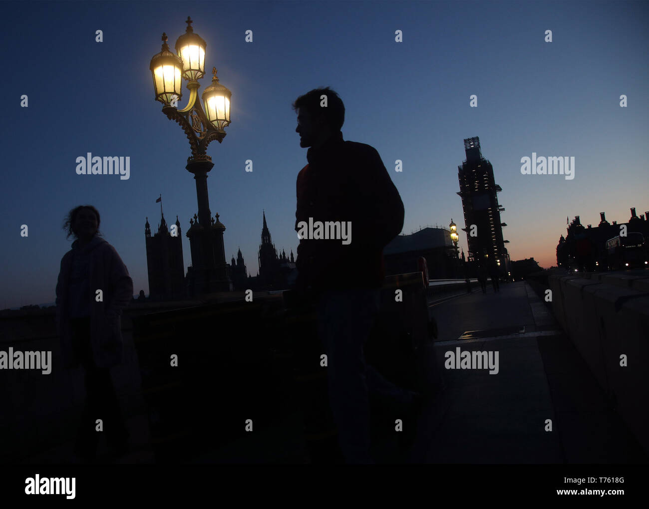 People are silhouetted at dusk on Westminster Bridge, in London. Parts of the UK could have the coldest ever start to the early May bank holiday as chilly weather hits the country. - Stock Image