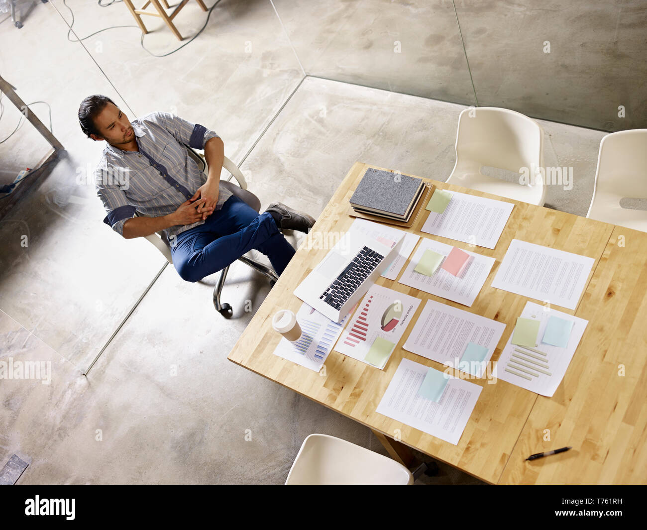 asian businessman in casual wear sitting alone in company meeting room thinking. - Stock Image
