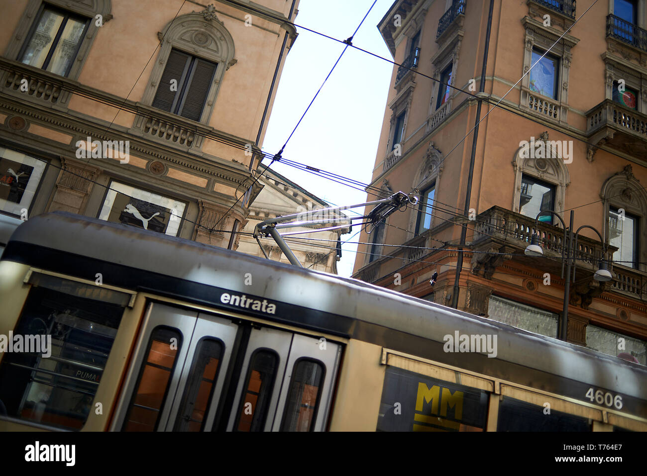 A tram driving through the streets surrounded by buildings in the city centre of Milan in Italy in daylight - Stock Image