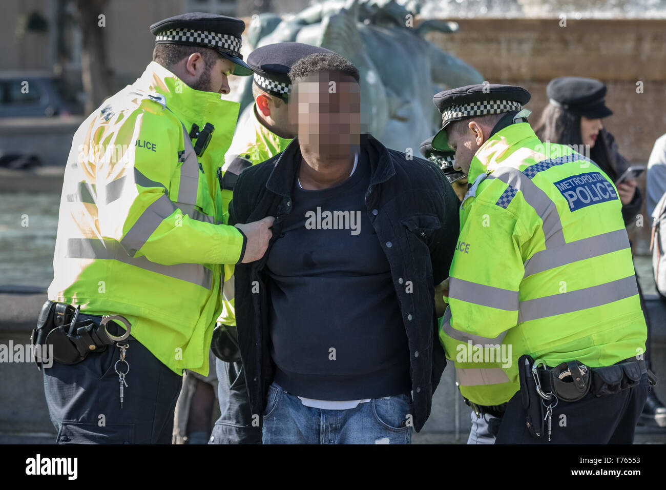 A young black male is stopped and searched during midday by four met police officers in Trafalgar Square, London, UK. - Stock Image