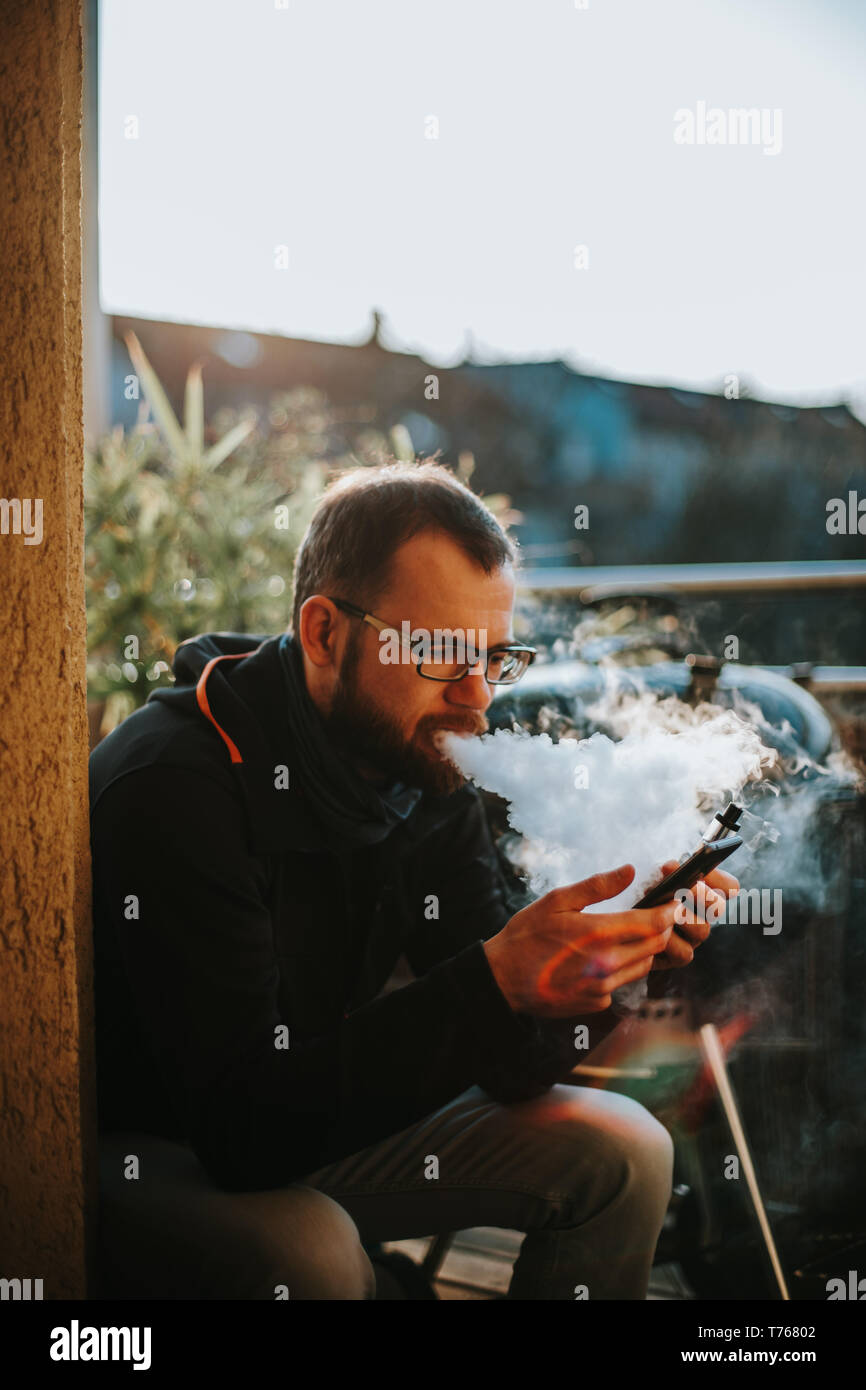 bearded caucasian man is smoking his e-cigarette while texting with his smartphone - Stock Image