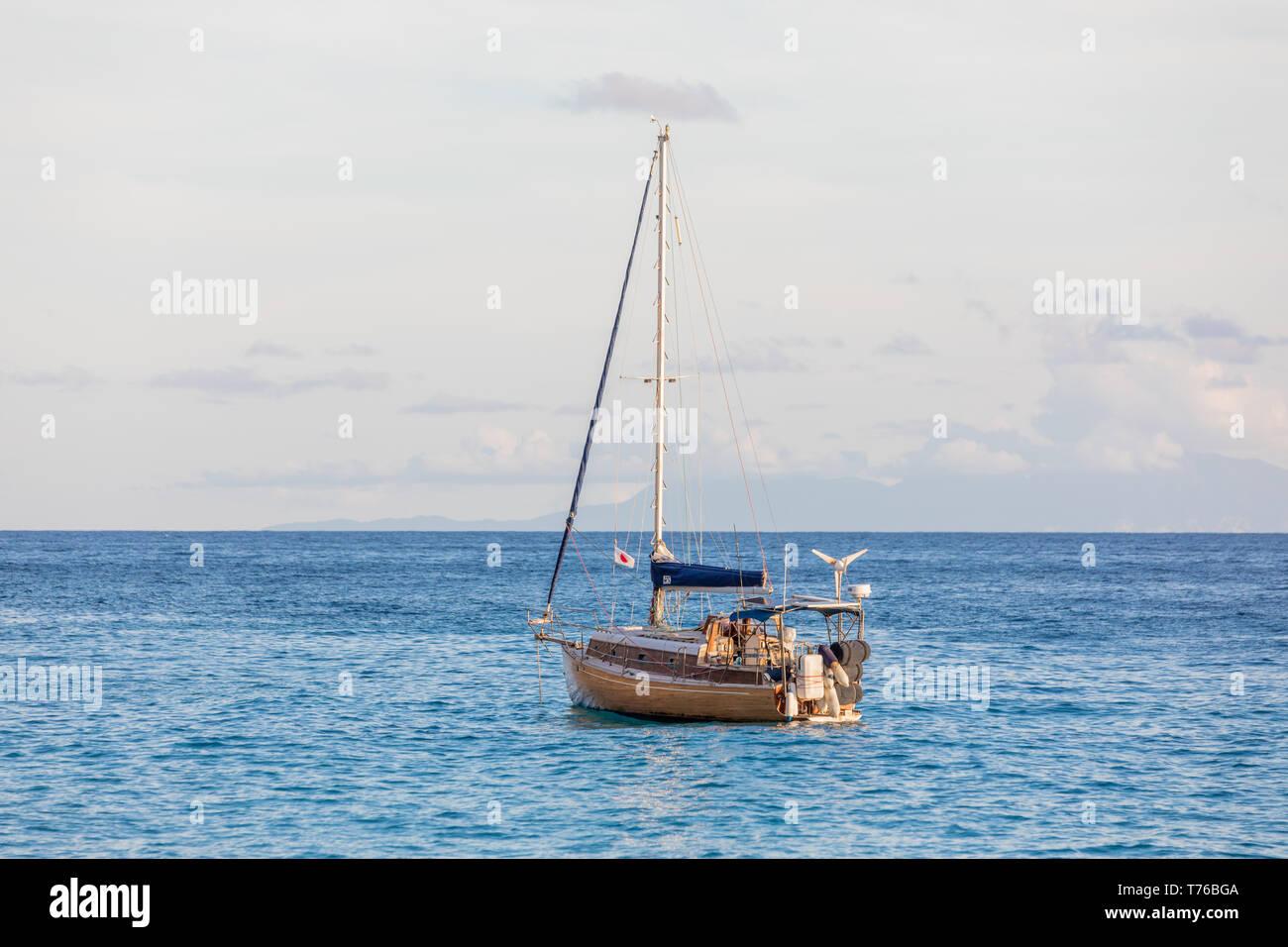 small sail boat at anchor off shell beach in St Barts Stock Photo