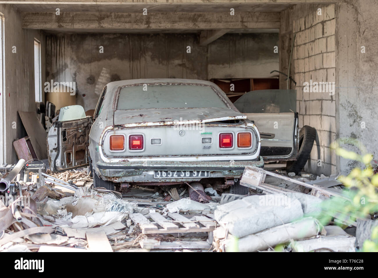 An old wrecked grey Mazada inside a ruined building in Gustavia St Barts - Stock Image
