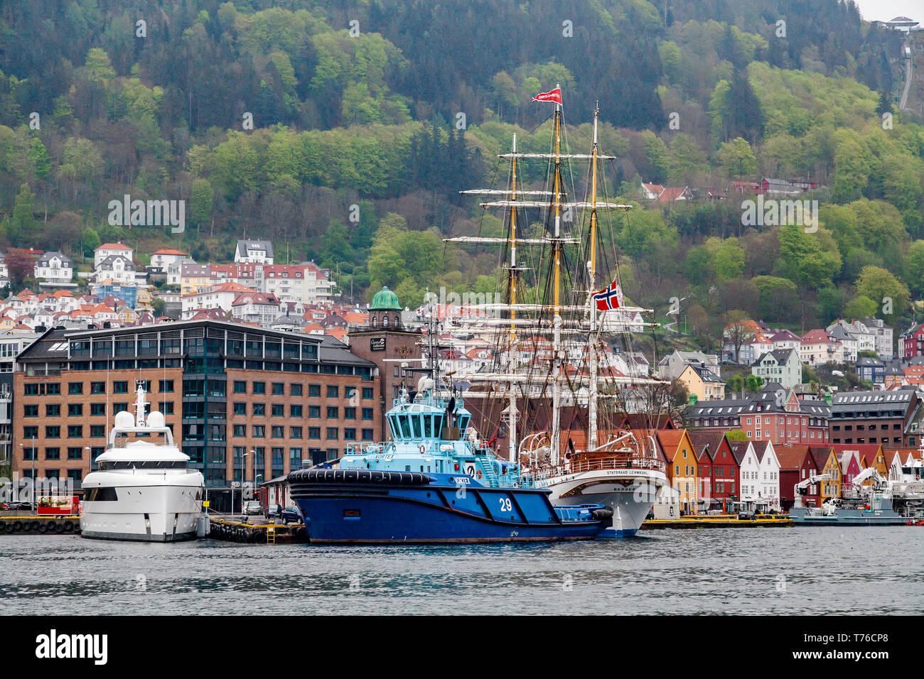 Tug boat Vortex at Bradbenken terminal in the port of Bergen, Norway. Tall ship Statsraad Lehmkuhl and super yacht Najiba in background. - Stock Image
