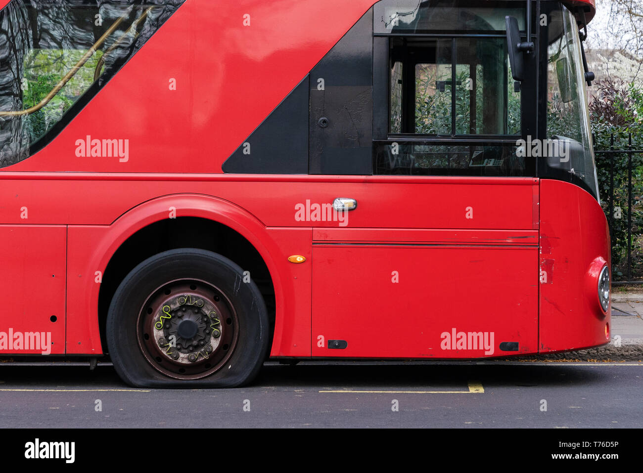 Flat tire on a red double decker bus in London. - Stock Image