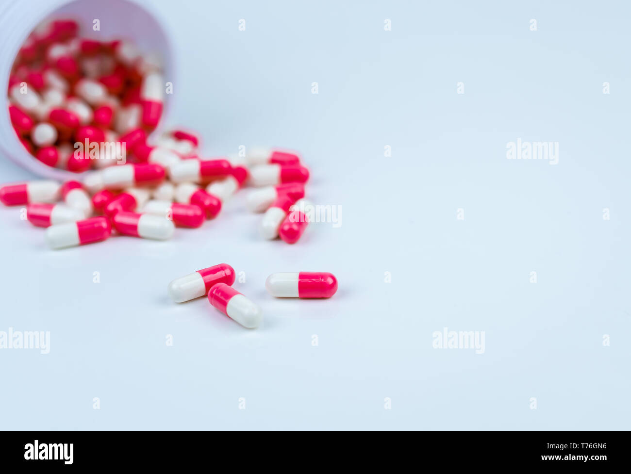 Pink and white capsules pill spilled out from white plastic bottle container. Global healthcare concept. Antibiotics drug resistance. Antimicrobial Stock Photo
