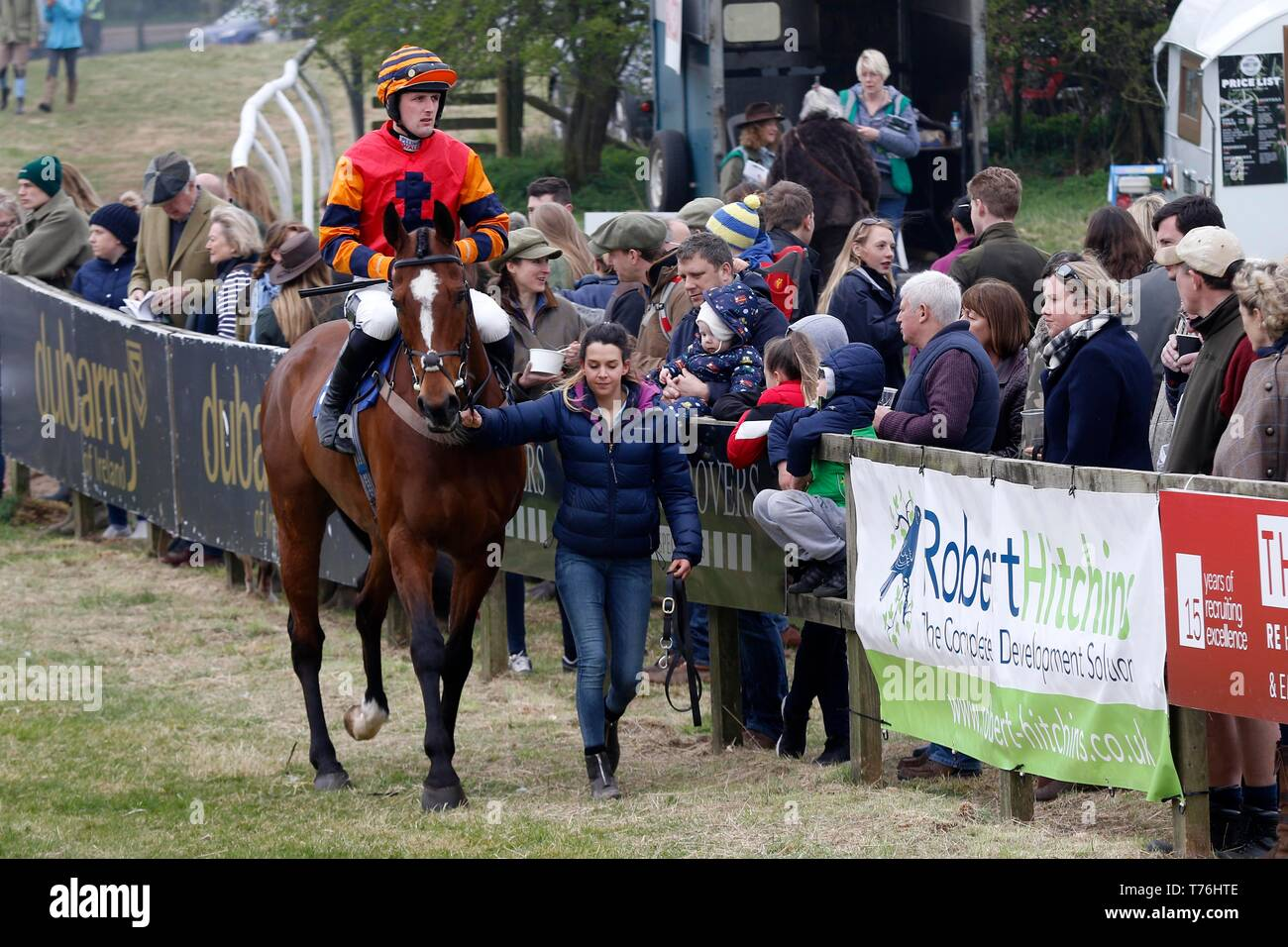 A horse and rider  being lead in the ring before their race at Andoversford Races, Gloucestershire. - Stock Image
