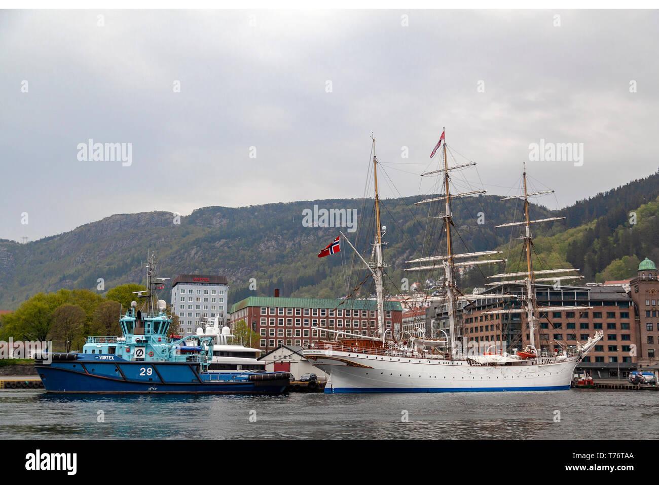 Tug boat Vortex at Bradbenken terminal in the port of Bergen, Norway.  Tall ship, sailship Statsraad Lehmkuhl. - Stock Image
