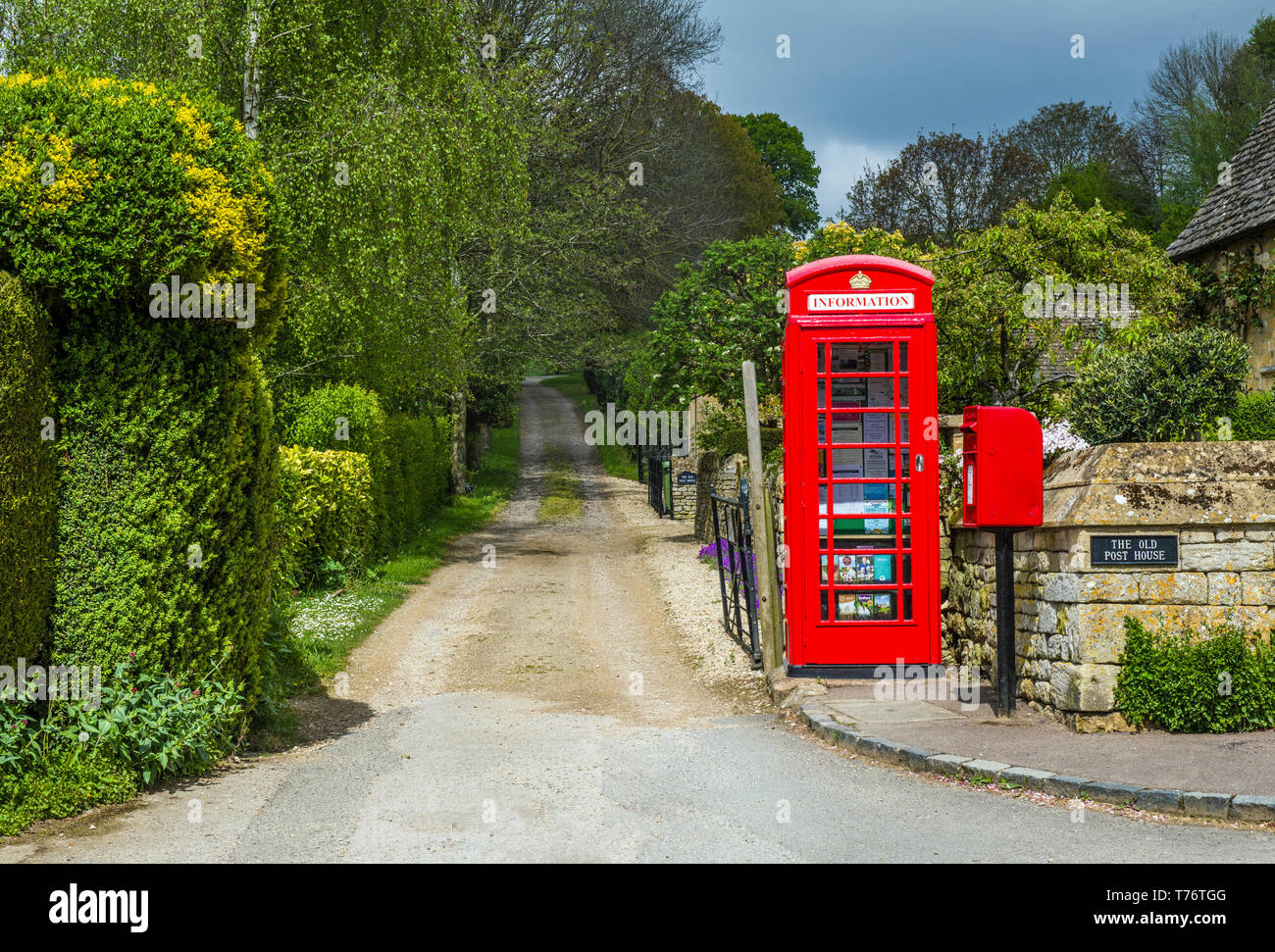 The Cotswold Village of Stanton, near Broadway, showing a lane with a red telephone box and red letterbox. The phone box contains visitor information. - Stock Image