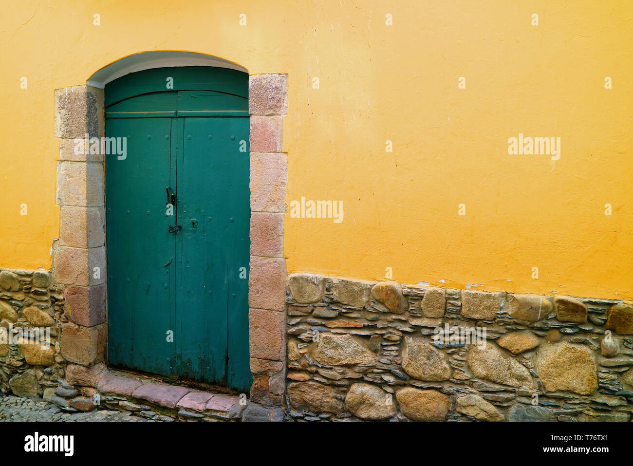 Green wooden door on the yellow wall of an old colonial building on Jaen street, La Paz, Bolivia - Stock Image