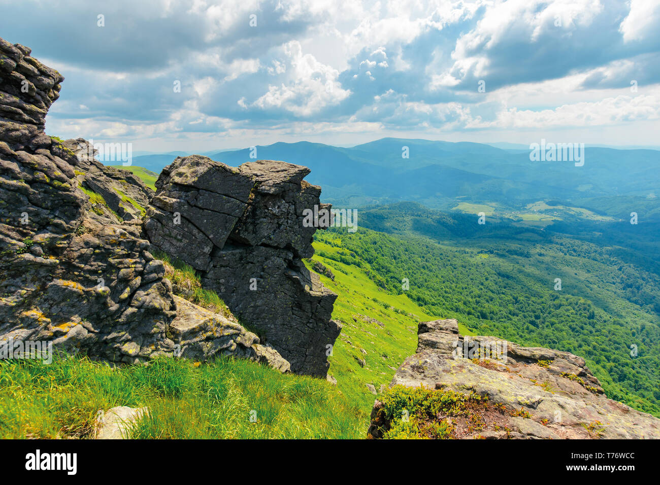 mountain summer landscape. meadow with huge boulders among the grass on top of the hillside near the peak of mountain ridge - Stock Image