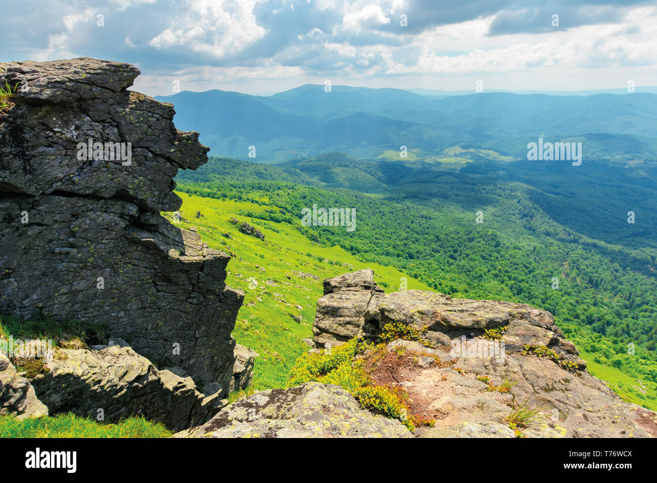 landscape with grassy meadow with giant boulders on the slope of a hill in Carpathian mountain ridge on a beautiful sunny summer day - Stock Image