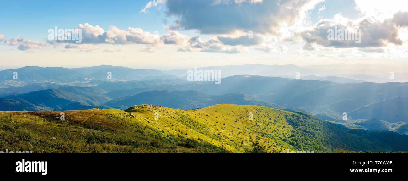 beautiful panorama of mountainous landscape. blue sky with some clouds over the grassy slope of a mountain ridge. lovely summer weather - Stock Image