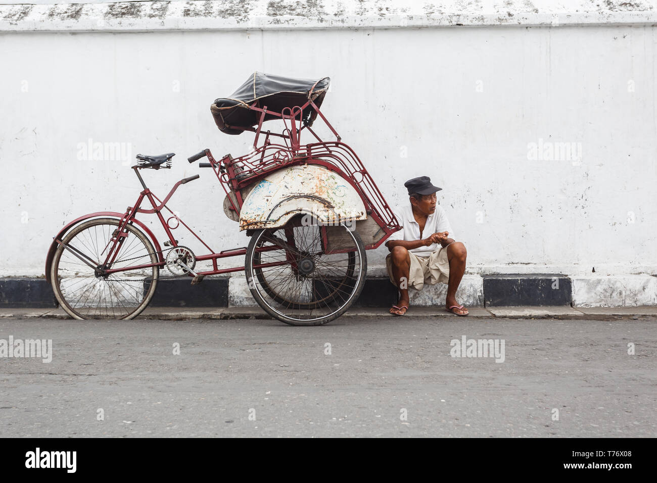 Driver of rickshaw bicycle taxi, sits on curb in street