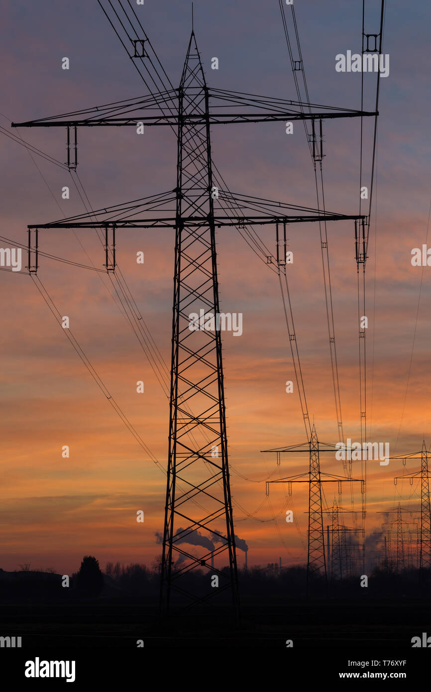 Silhouette of high voltage power lines and pylons leading to a steam power station in front of a colorful after sunset sky. Karlsruhe, Germany Stock Photo