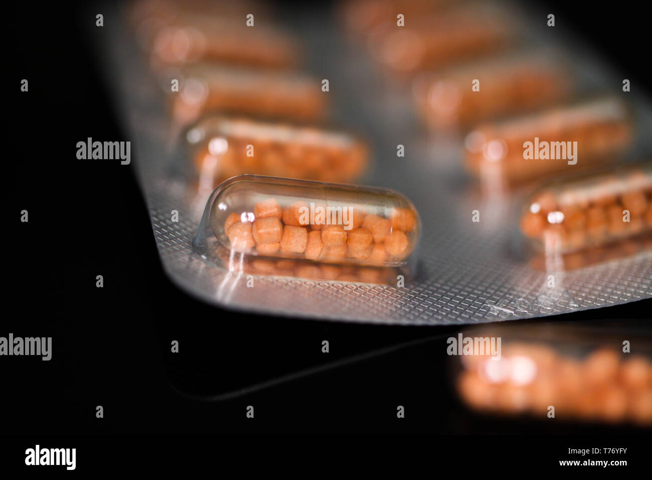 Makro close up of capsule pills in silver blister package and one isolated capsule with black reflecting background. Transparent shell showing pearls  - Stock Image