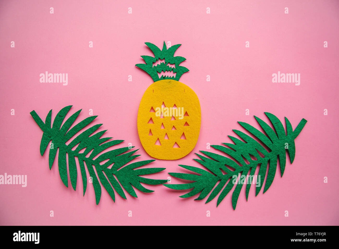 Felt tropical leaves Fern and pineapple on a pink background in minimal style. Summer design. - Stock Image
