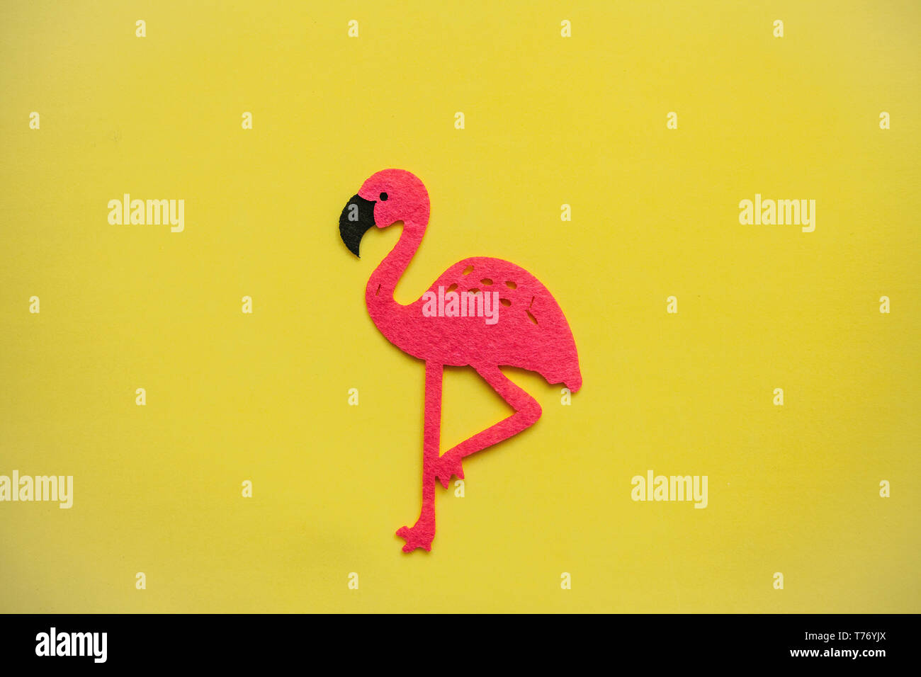 Felt pink flamingo on a yellow background in minimal style. - Stock Image