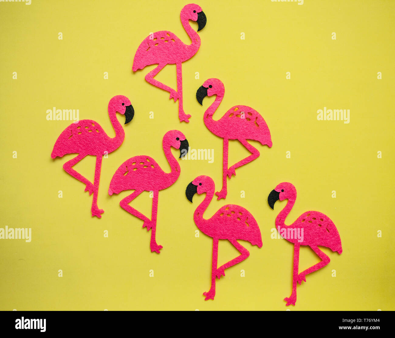 Many felt pink flamingos on a yellow background. Summer design. - Stock Image